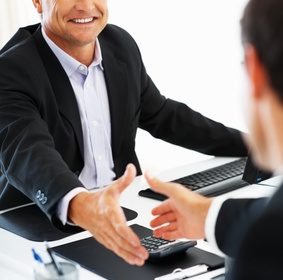 Mature business man shaking hands with colleague across the table