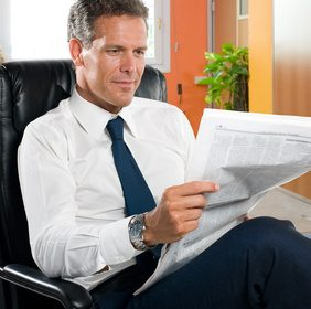Businessman reading news while taking a break in his office